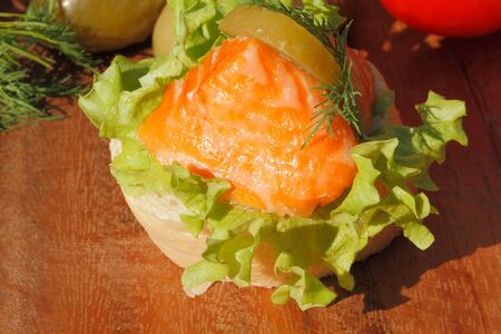 salmon filet: Slice of baguette with smoked salmon filet, garnished with lettuce, onion, tomato and pickles on a wooden board
