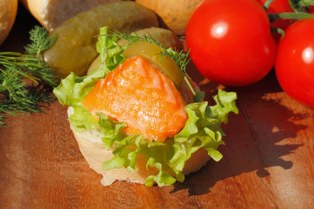 Slice of baguette with smoked salmon filet, garnished with lettuce, onion, tomato and pickles on a wooden board