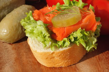 Slice of baguette with pollock fillet, garnished with lettuce, onion, tomato and pickles on a wooden board Stock Photo