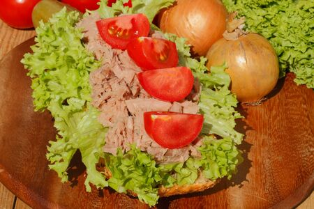 Fish rolls with tuna fillet garnished with lettuce, tomato, onion and pickles on a wooden board Stock Photo