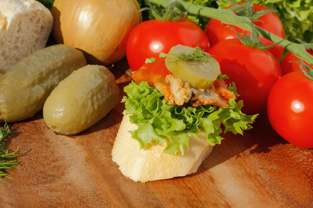 garnished: Slice of baguette with Herring fillets in tomato sauce, garnished with lettuce, onion, tomato and pickles on a wooden board Stock Photo