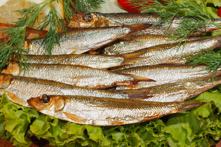 sprats: Smoked sprat with salad, lemon, onions tomato, garnished with dill on a wooden kitchen board