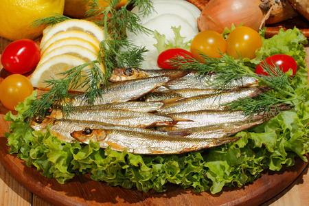 sprat: Smoked sprat with salad, lemon, onions tomato, garnished with dill on a wooden kitchen board