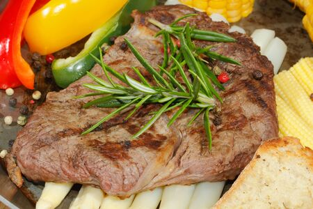 corncob: Grilled beef steak with asparagus, peppers, corncob in a pan