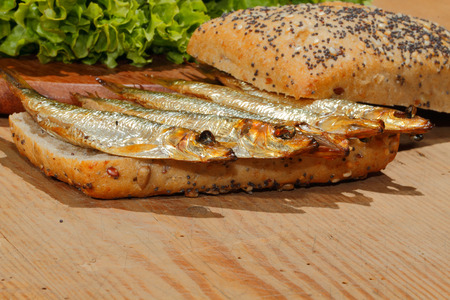 sprat: Smoked sprat in whole wheat bread, with lettuce on a wooden chopping board