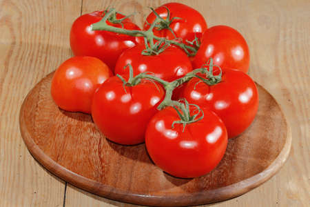 chopping board: Tomatoes panicles on a wooden chopping board