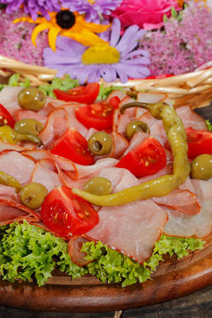 Ham plate, ham, pepperoni, tomatoes, olive, lettuce, garnished with mint Stock Photo
