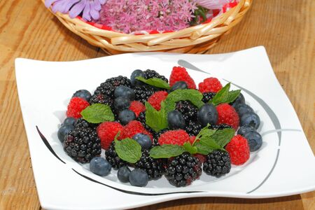 Blueberries, raspberries, blackberries, garnished with mint leaves on a plate