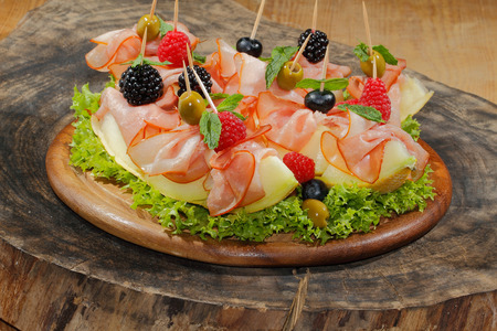 Galia melon, melon with ham, garnished with raspberries, blueberries, blackberries and olives on a plate