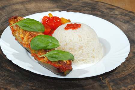 Stuffed zucchini, rice, stewed peppers and tomatoes, vegetables, side dish, garnished with basil leaves on a plate