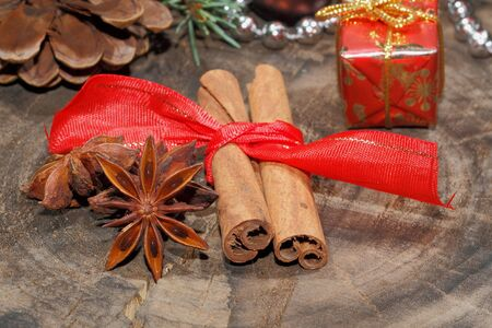 dried herbs: Cinnamon sticks, anise stars, nuts and christmas decoration on a rustic, wooden plate