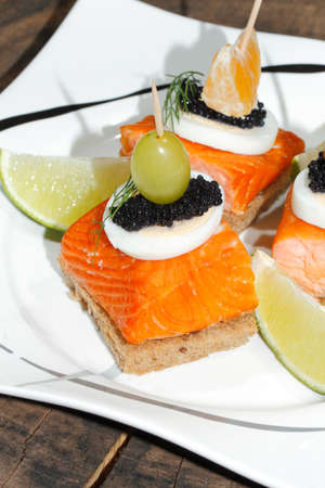 Toast with smoked salmon, garnished with egg, orange, olive, grape, lemon and caviar on a plate