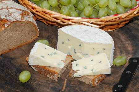 Blue cheese, bread, grapes on a rustic kitchen board