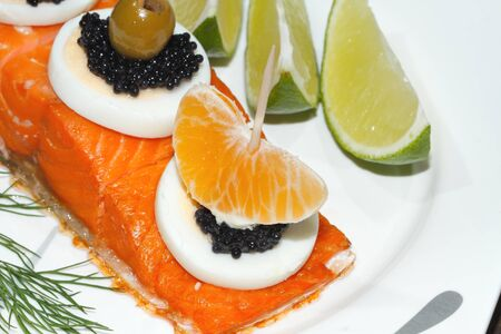 Smoked salmon, garnished with egg, orange, olive, grape, lemon and caviar on a plate