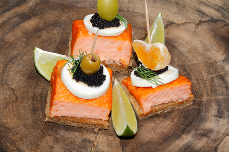 Slice of Toast with smoked salmon, garnished with egg, orange, grape, olive, lemon and caviar on a wooden board