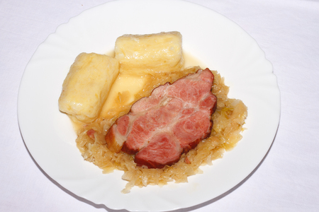 A slice of roast pork with potato dumplings and pickled cabbage on a plate Stock Photo