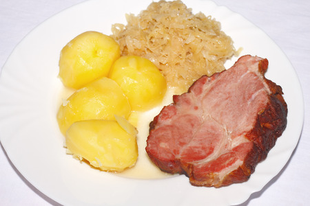 A slice of roast pork with potatos and pickled cabbage on a plate