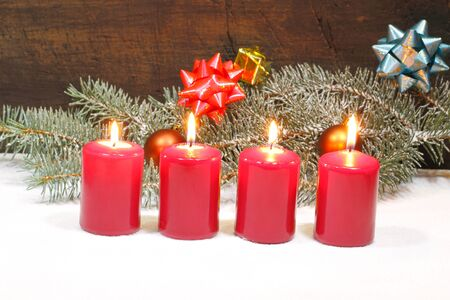 Advent candles with fir green and Christmas decoration in snow