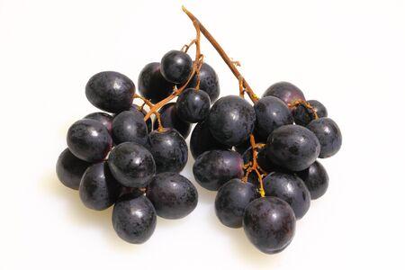 Blue grapes on a white plastic kitchen board