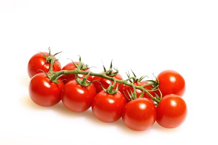 panicle: Panicle with tomatoes on a white cutting board made of plastic Stock Photo