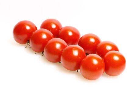 Panicle with tomatoes on a white cutting board made of plastic Stock Photo