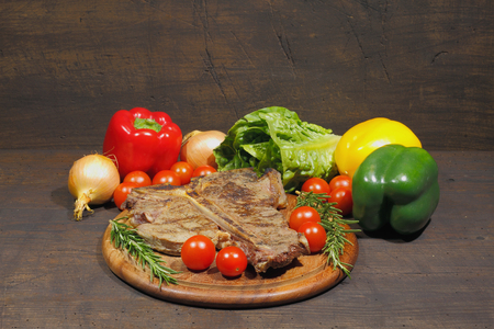 Grilled T bone steak with rosemary tomatoes, onions and pepper garnished, on a rustic wooden chopping board Stock Photo