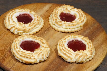 Coconut tartlets stuffed with strawberry jam on a rustic, wooden surface