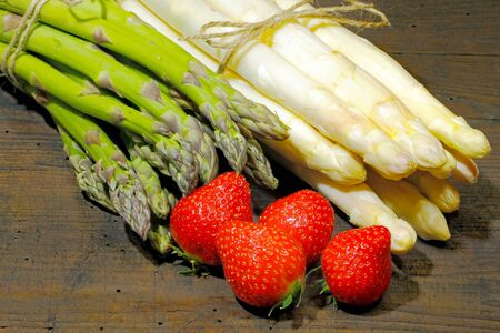 Freshly harvested asparagus and strawberries on a rustic, old wooden board