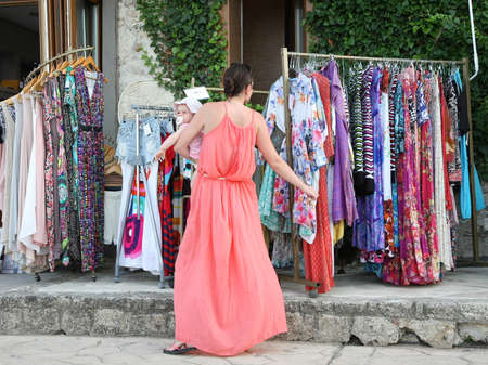 browses: Mother with her baby girl browses clothes in the street  shop