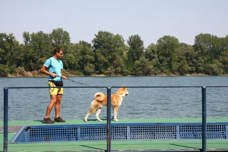 aggressiveness: Akita Inu puppy with its owner standing by the river Stock Photo