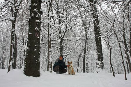 a blizzard: Akita Inu and its owner in public park during  blizzard