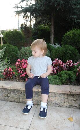 babyhood: Cute baby girl sitting on the wall