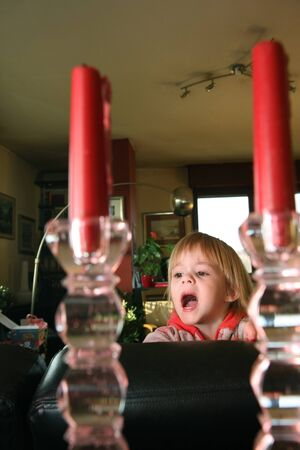clowning: Young girl clowning between two candles