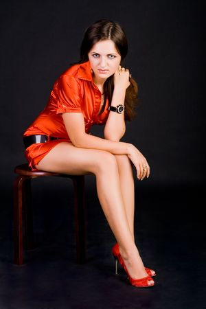 Photo of the sitting girl in red dress and shoes Stock Photo