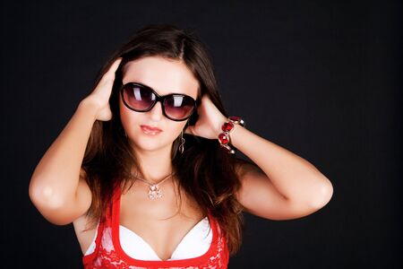 Portrait of the girl in a red blouse and in sunglasses on black background photo