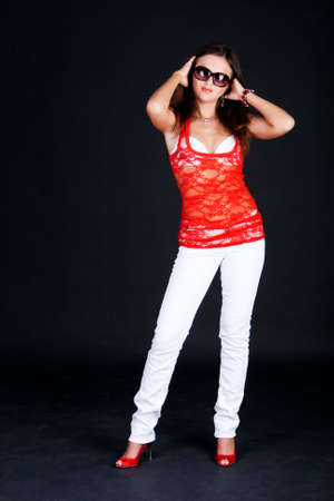 Photo of standing girl in a red blouse and in sunglasses on black background photo