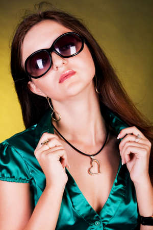 blouse sexy: Portrait of a young brunette with a neckline in sunglasses and a green blouse