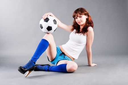 Portrait of charming beautiful young girl in a blue shorts and with a soccer ball.