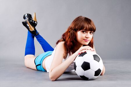 Lying young girl on floor with a soccer ball  photo