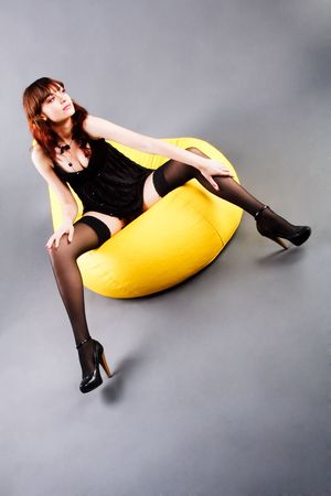 Picture of a beautiful adorable young girl in black tunic whit sits on yellow soft armchair