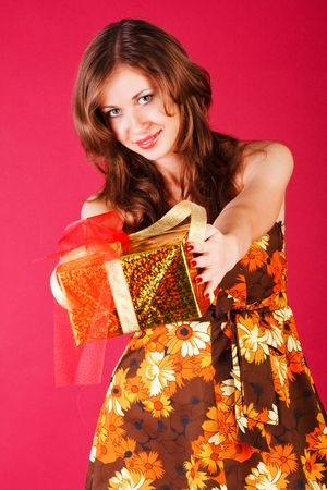 Picture of a beautiful adorable young girl in dress with a present photo