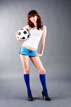 Picture of a charming young girl in a blue shorts and with a soccer ball. photo