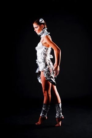 Picture of a beautiful young girl in foil dress on black background. Stock Photo - 6134192