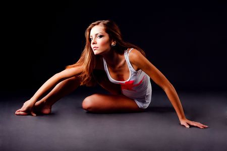 Picture of a beautiful young girl in white shirt sits on floor