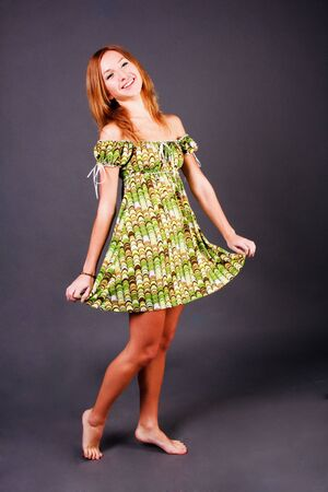 Picture of a beautiful adorable young girl in green dress on grey background photo