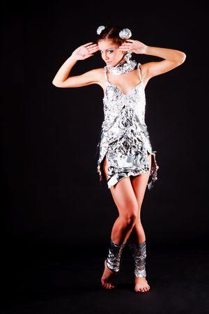 Image d'une belle jeune fille dans la robe de papier aluminium sur fond noir. Banque d'images