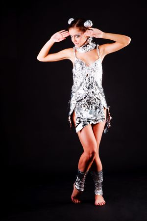 Picture of a beautiful young girl in foil dress on black background. Stock Photo