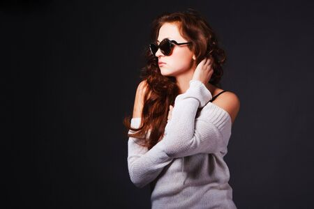 Portrait of a attractive young girl in sunglasses on grey background. photo
