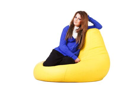 Picture of a charming young girl in blue on armchair. White background.