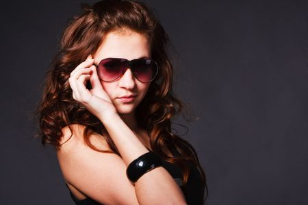 Portrait of a charming young girl in glasses on grey background.